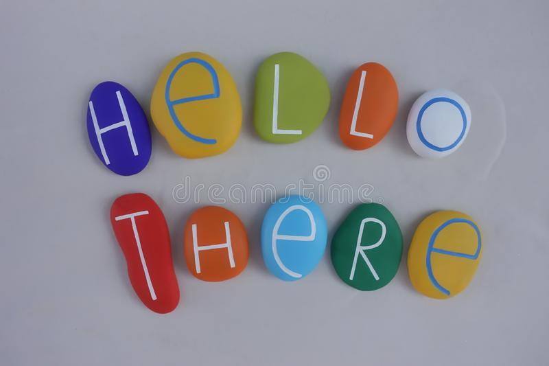 Bonjour là textotent avec une composition des pierres colorées au-dessus du sable blanc photographie stock libre de droits