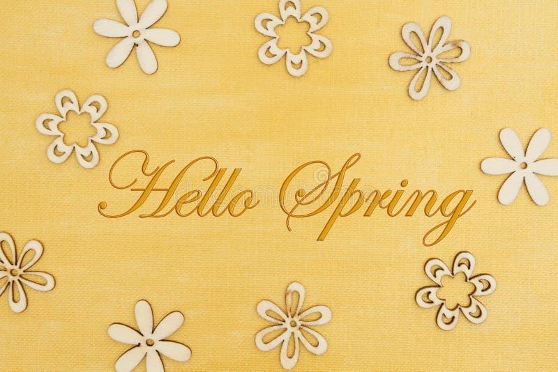 Bonjour le message de ressort avec les pétales en bois de fleur a en main peint l'or affligé photos stock