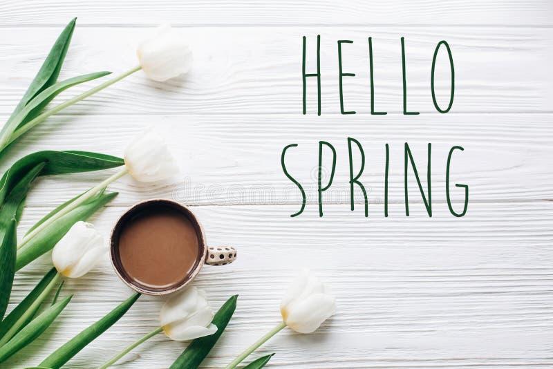 Bonjour le texte de ressort se connectent les tulipes et le café sur la rouille en bois blanche photographie stock libre de droits