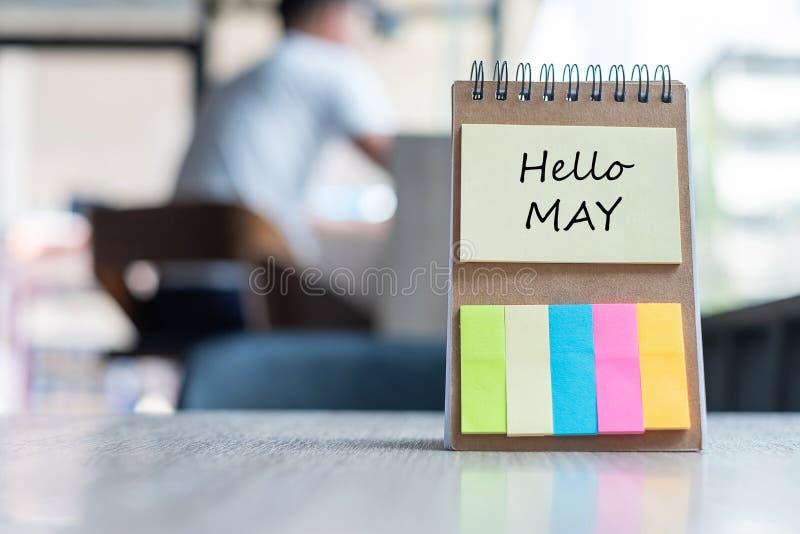 Bonjour mai avec le calibre de rappel de papier de note avec le stylo sur la table en bois copiez l'espace pour votre texte images libres de droits