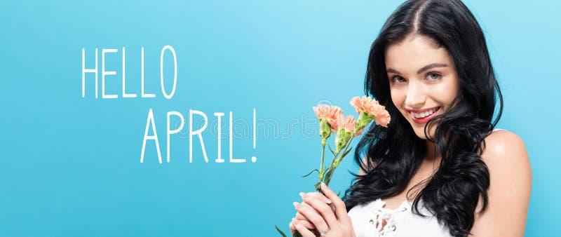Bonjour message d'avril avec la jeune femme tenant des oeillets photographie stock libre de droits
