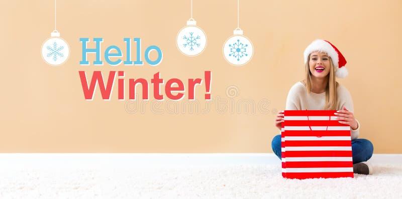Bonjour message d'hiver avec la femme avec le chapeau de Santa tenant un sac à provisions image stock