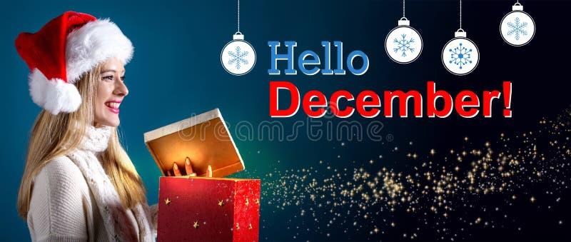 Bonjour message de décembre avec la femme ouvrant un boîte-cadeau photos stock