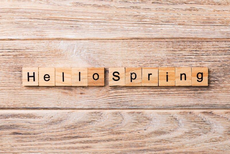 Bonjour mot de ressort écrit sur le bloc en bois Bonjour texte de ressort sur la table en bois pour votre desing, concept photos stock
