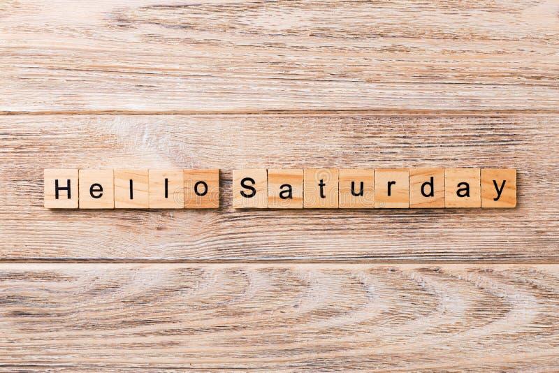 Bonjour mot de samedi écrit sur le bloc en bois bonjour texte de samedi sur la table en bois pour votre desing, concept photo libre de droits