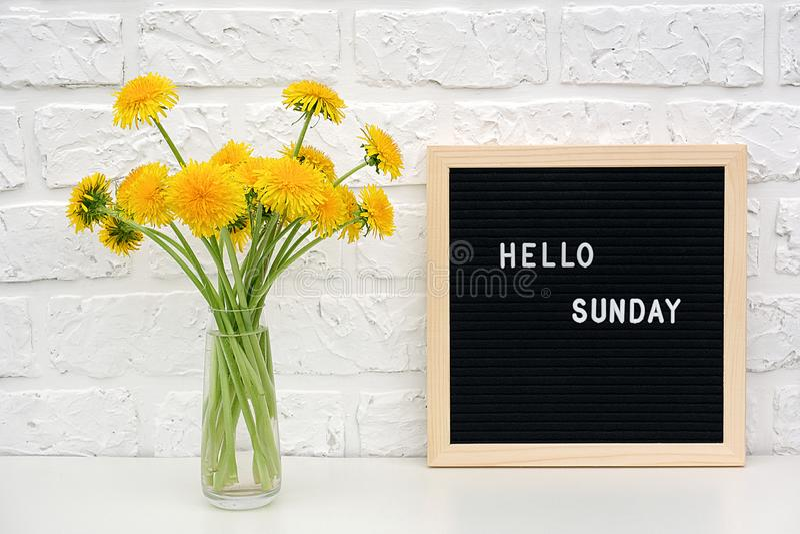 Bonjour mots de dimanche sur le panneau de lettre noire et le bouquet des fleurs jaunes de pissenlits sur la table contre le mur  photos libres de droits
