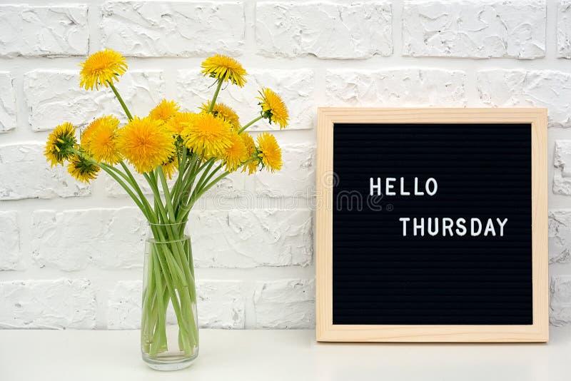 Bonjour mots de jeudi sur le panneau de lettre noire et le bouquet des fleurs jaunes de pissenlits sur la table contre le mur de  images stock