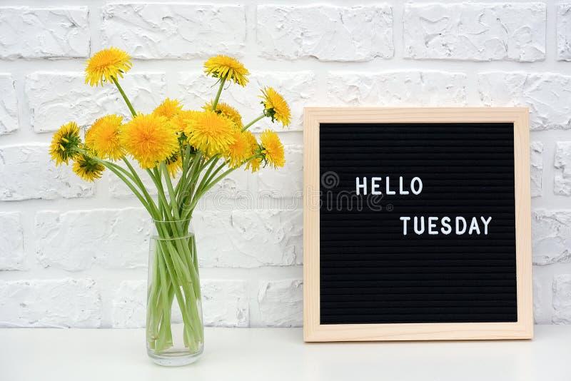 Bonjour mots de mardi sur le panneau de lettre noire et le bouquet des fleurs jaunes de pissenlits sur la table contre le mur de  photographie stock libre de droits