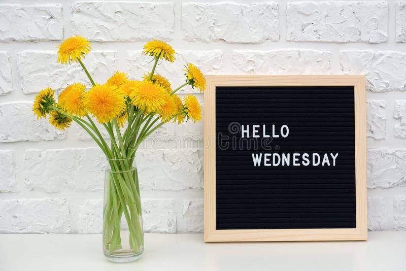 Bonjour mots de mercredi sur le panneau de lettre noire et le bouquet des fleurs jaunes de pissenlits sur la table contre le mur  photo stock