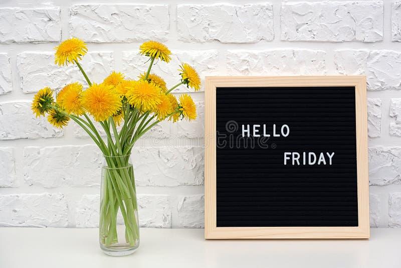 Bonjour mots de vendredi sur le panneau de lettre noire et le bouquet des fleurs jaunes de pissenlits sur la table contre le mur  photographie stock libre de droits