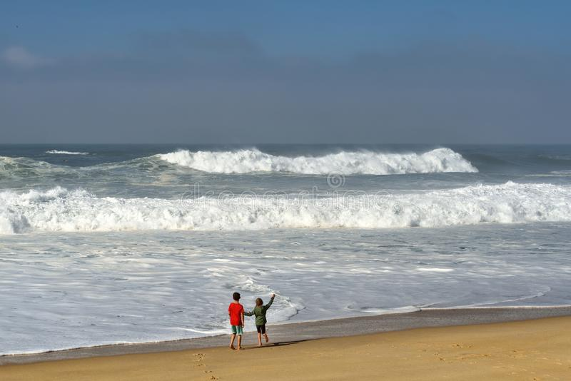 Bonjour océan ! Enfants regardant fixement le grand ressac photo libre de droits