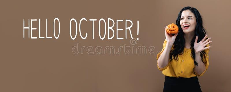 Bonjour octobre avec la femme tenant un potiron photos libres de droits