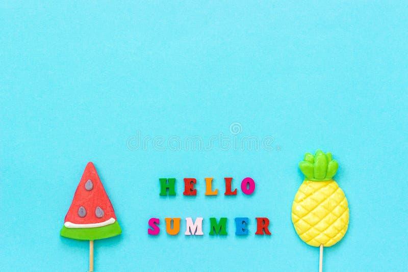 Bonjour texte d'été, ananas et lucettes colorés de pastèque sur le bâton sur le fond de papier bleu Vacances ou vacances de conce images stock