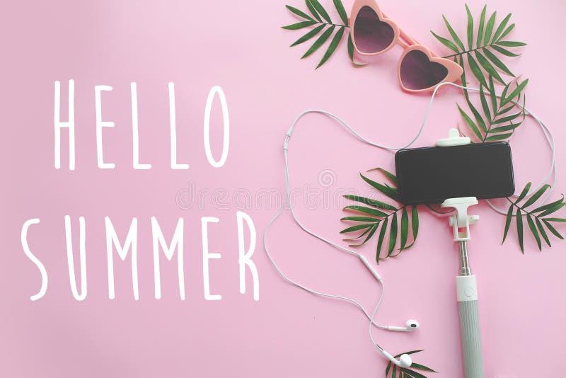 Bonjour texte d'été sur les lunettes de soleil roses élégantes, téléphone sur le St de selfie photographie stock libre de droits