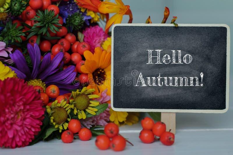 Bonjour texte d'automne sur le mini tableau et les fleurs colorées sur la table image stock