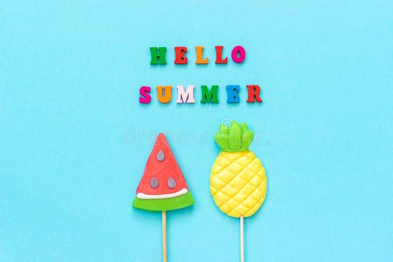 Bonjour texte d'?t?, ananas et lucettes color?s de past?que sur le b?ton sur le fond de papier bleu Vacances ou vacances de conce images stock