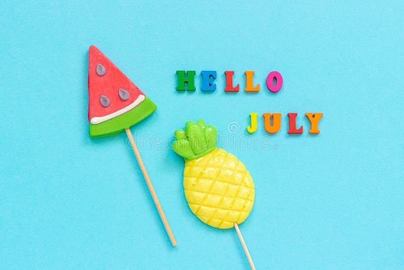 Bonjour texte de juillet, ananas et lucettes color?s de past?que sur le b?ton sur le fond de papier bleu Vacances de concept ou image libre de droits