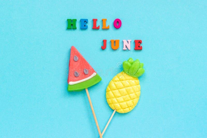 Bonjour texte de juin, ananas et lucettes color?s de past?que sur le b?ton sur le fond de papier bleu Vacances ou vacances de con photo stock