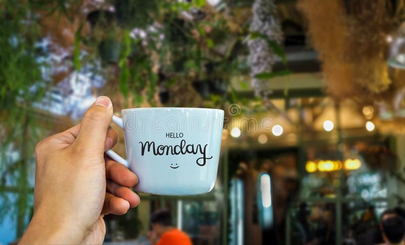 Bonjour texte de lundi sur la main de tasse de café se tenant en café photo stock