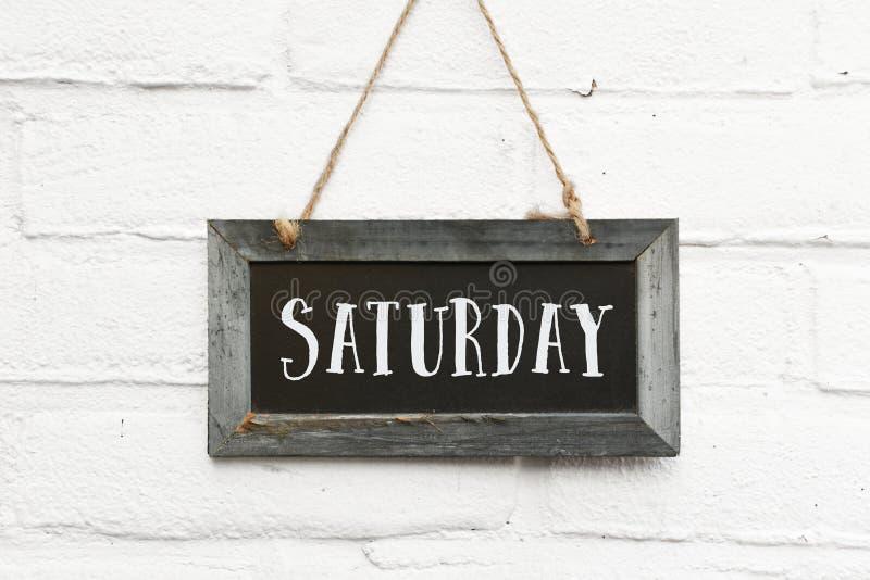 Bonjour texte de samedi sur le mur extérieur accrochant de brique blanche de conseil photo stock