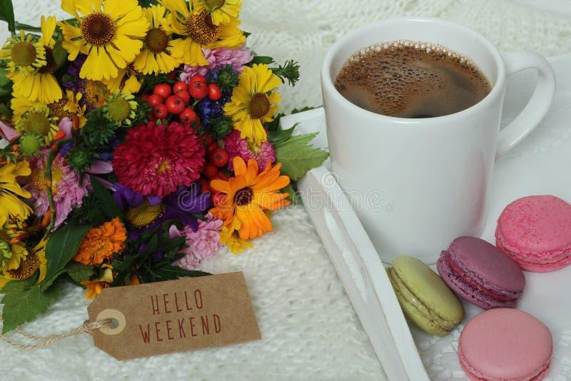 Bonjour texte de week-end sur le label, les fleurs d'automne, la tasse de café et les macarons photographie stock libre de droits