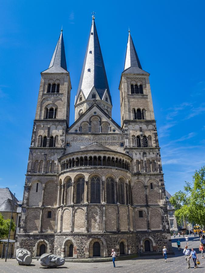 The Bonn Minster with the sculptures depicting the heads of Saints Cassius and Florentius in front, in Bonn, Germany. BONN, GERMANY - JUNE 06, 2014: The Bonn stock images