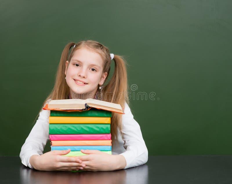 Bonne écolière avec des tas de livres près d'un tableau vert vide images stock