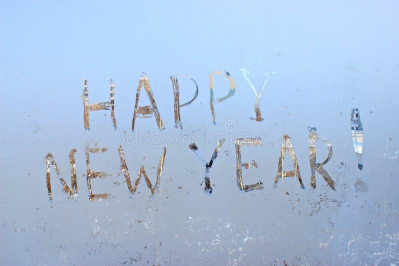 Bonne année écrite sur le fond givré de fenêtre d'hiver photographie stock