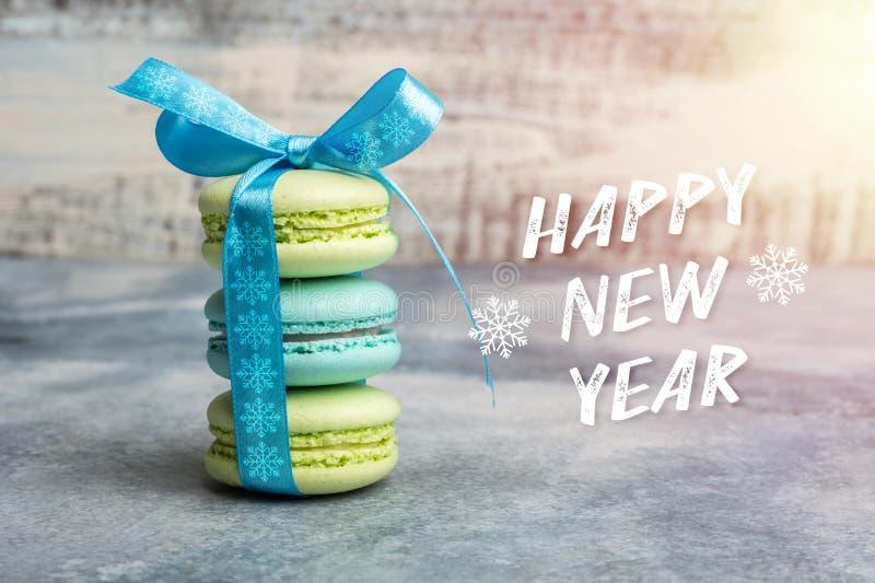 Bonne année de carte de voeux trois macarons sont attachés par un ruban bleu image libre de droits
