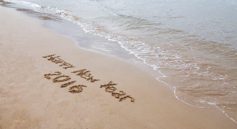 Bonne année dessinée sur le sable image stock