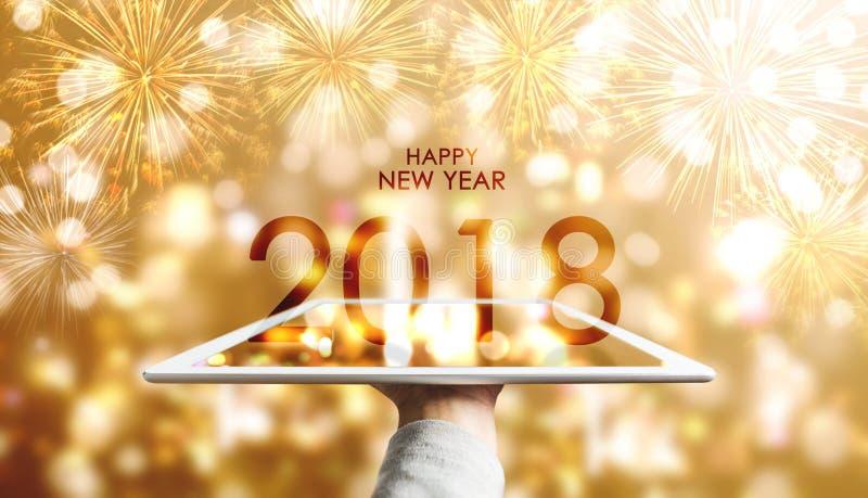 Bonne année 2018, main tenant le comprimé numérique avec le fond de luxe de feux d'artifice de Bokeh d'or images stock