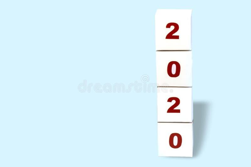 Bonne année 2020 sur un bloc cubique de livre blanc sur un fond bleu lumineux, carte de voeux 2020, bannière de bonne année copie photographie stock libre de droits