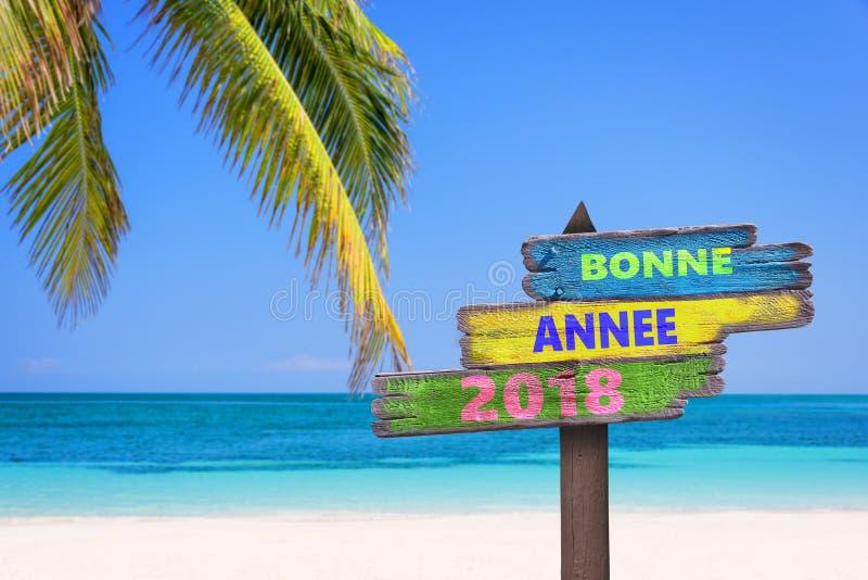 Bonne annee 2018新年好用法语在色的木方向标、海滩和棕榈树背景 库存照片