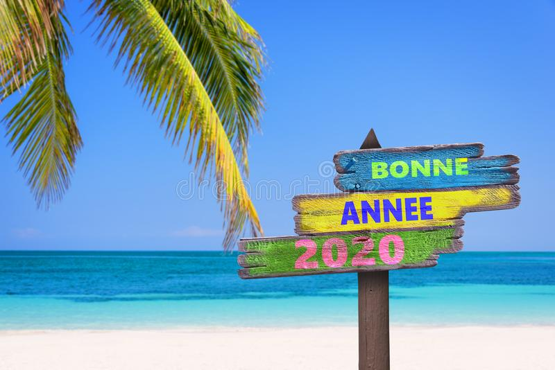 Bonne annee 2020, meaning happy new year in French, on direction signs tropical beach background royalty free stock photography