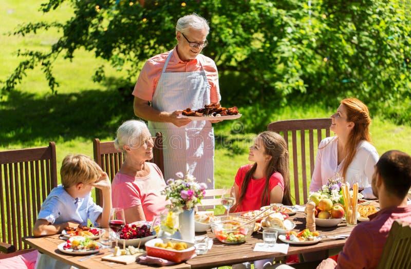 Bonne famille à dîner ou à la fête du jardin d'été image libre de droits