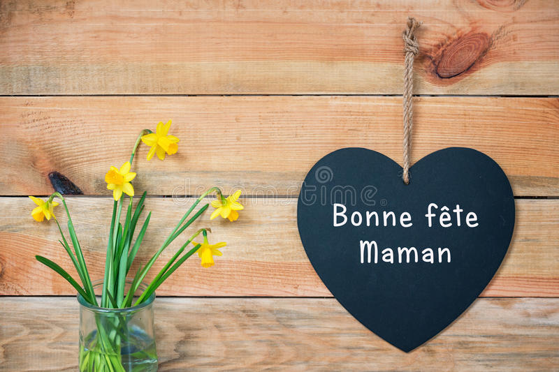 Bonne fete maman, French mothers day card, wood planks with daffodils and a blackboard in shape of a heart. Bonne fete maman, French mothers day card, wood stock photos