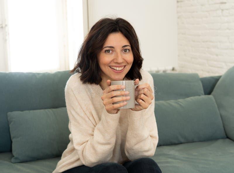 Bonne jeune femme assise sur un canapé à la maison avec une boisson chaude Concept de loisirs et de temps libre photos libres de droits