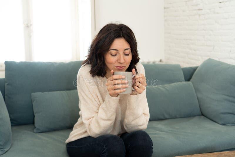 Bonne jeune femme assise sur un canapé à la maison avec une boisson chaude Concept de loisirs et de temps libre image stock