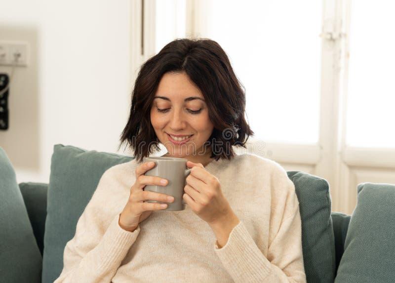 Bonne jeune femme assise sur un canapé à la maison avec une boisson chaude Concept de loisirs et de temps libre images stock