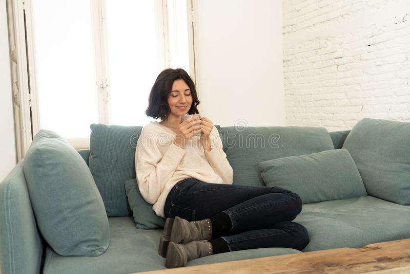 Bonne jeune femme assise sur un canapé à la maison avec une boisson chaude Concept de loisirs et de temps libre image libre de droits