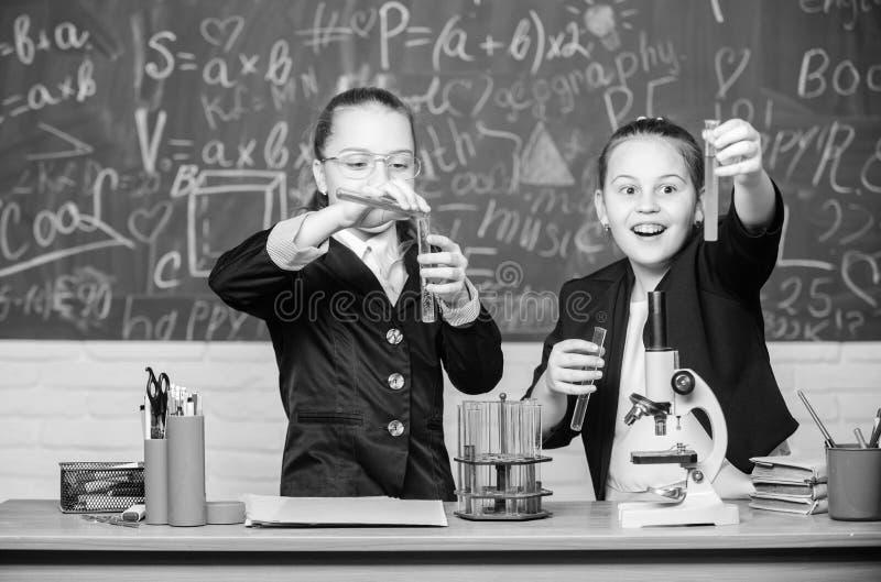 Bonne nouvelle expérimentation scientifique en laboratoire Recherche en chimie Les petites filles scientifiques travaillent au mi photos stock