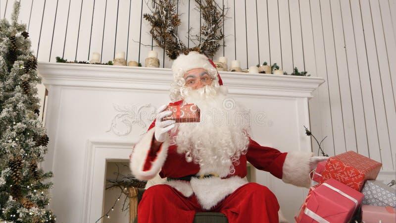 Bonne vieille Santa Claus s'asseyant dans une chaise par la description de cheminée quels présents il a préparés pour Noël images stock
