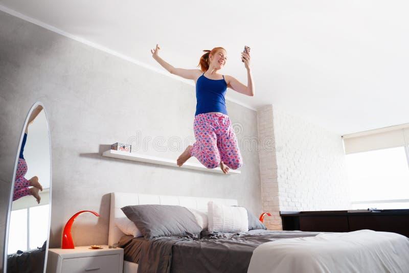 Bonnes actualités pour la fille heureuse de jeune femme sautant sur le lit image stock