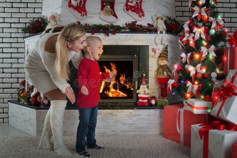 Bonnes fêtes ! Le petit enfant mignon ainsi que la mère a trouvé beaucoup de cadeaux sous l'arbre de Noël photographie stock libre de droits