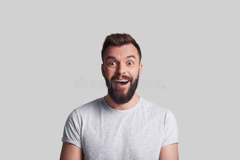 Bonnes nouvelles Jeune homme choqué regardant l'appareil-photo et souriant tandis que image libre de droits