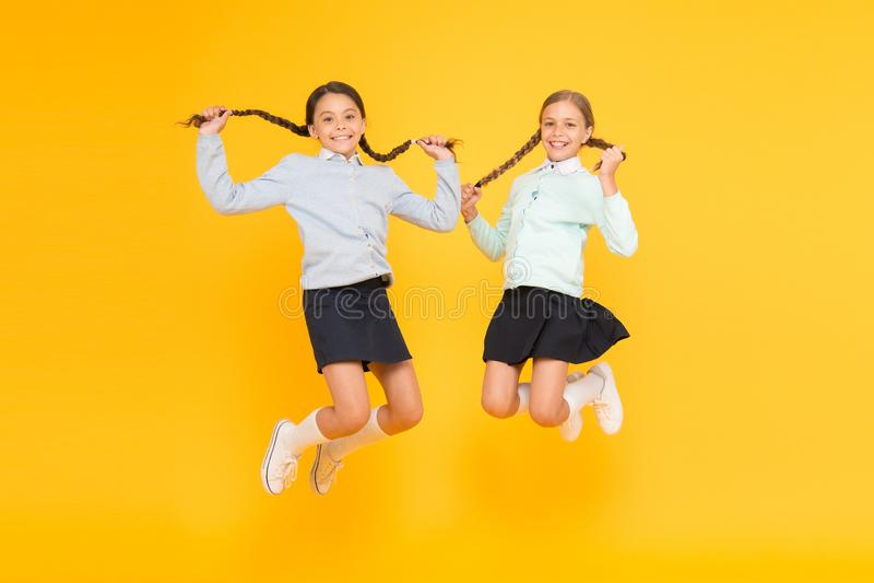 Bons cheveux fabuleux se sentants Petits enfants mignons avec les cheveux tressés sautant sur le fond jaune Petites filles heureu photos stock
