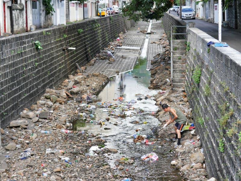 Bons drains de dégagement samaritains d'homme responsable de citoyen sur le Port-Louis Îles Maurice images libres de droits