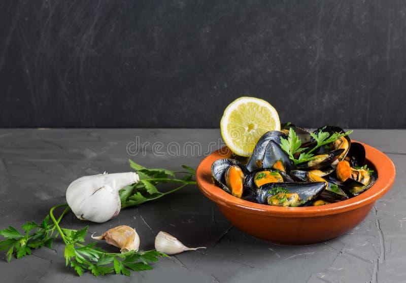 Bons mexilhões de Taranto em uma placa com salsa, alho e limão, cópia-espaço imagens de stock royalty free