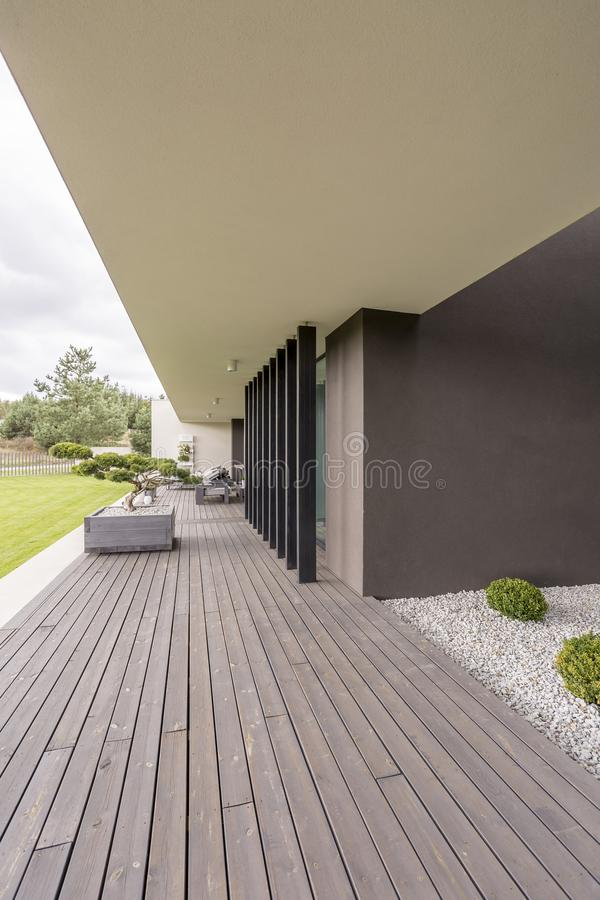 Bonsai tree on terrace. Side view of wooden board floor and black pillars of terrace with Bonsai tree royalty free stock photos