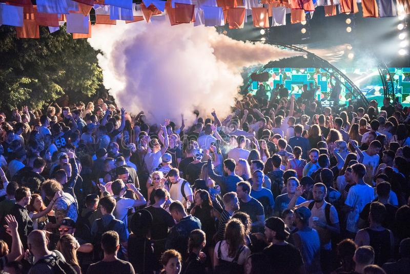 People clubbing and having fun. BONTIDA, ROMANIA - JULY 20, 2018: Crowd of people dancing and clubbing at Electric Castle festival during a Dj Heion concert royalty free stock photography
